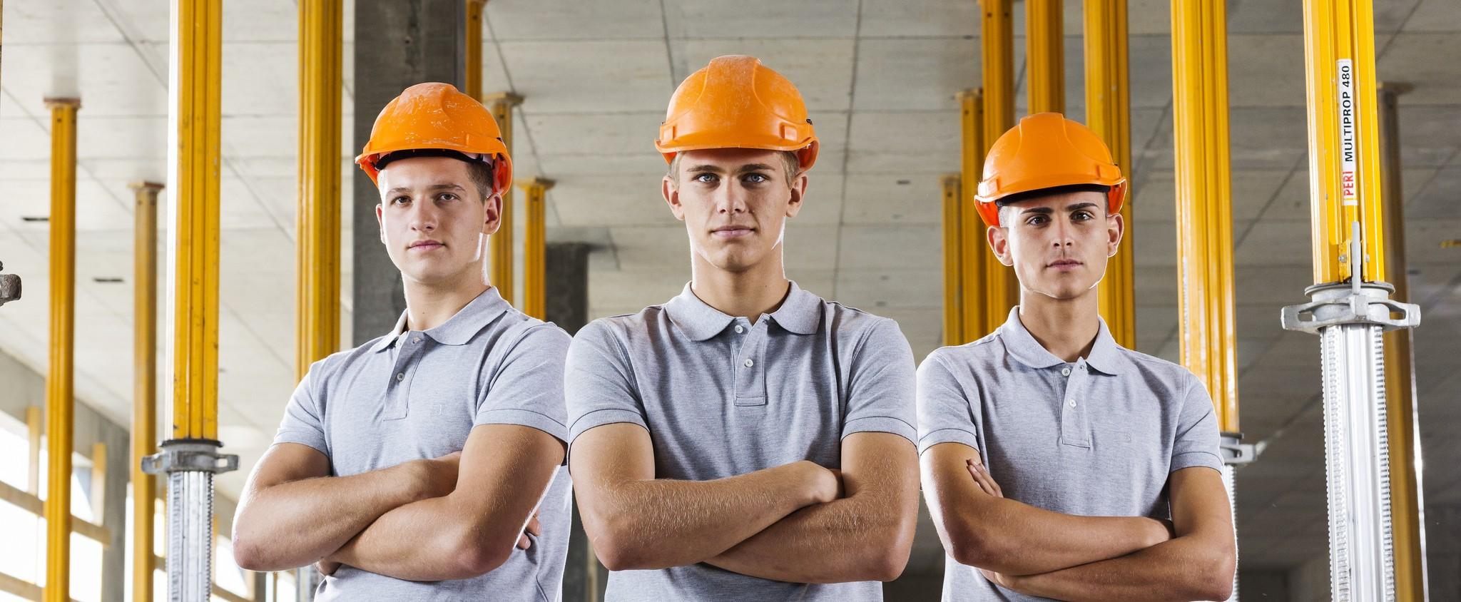 Drei junge Bauarbeiter mit orangen Helmen.