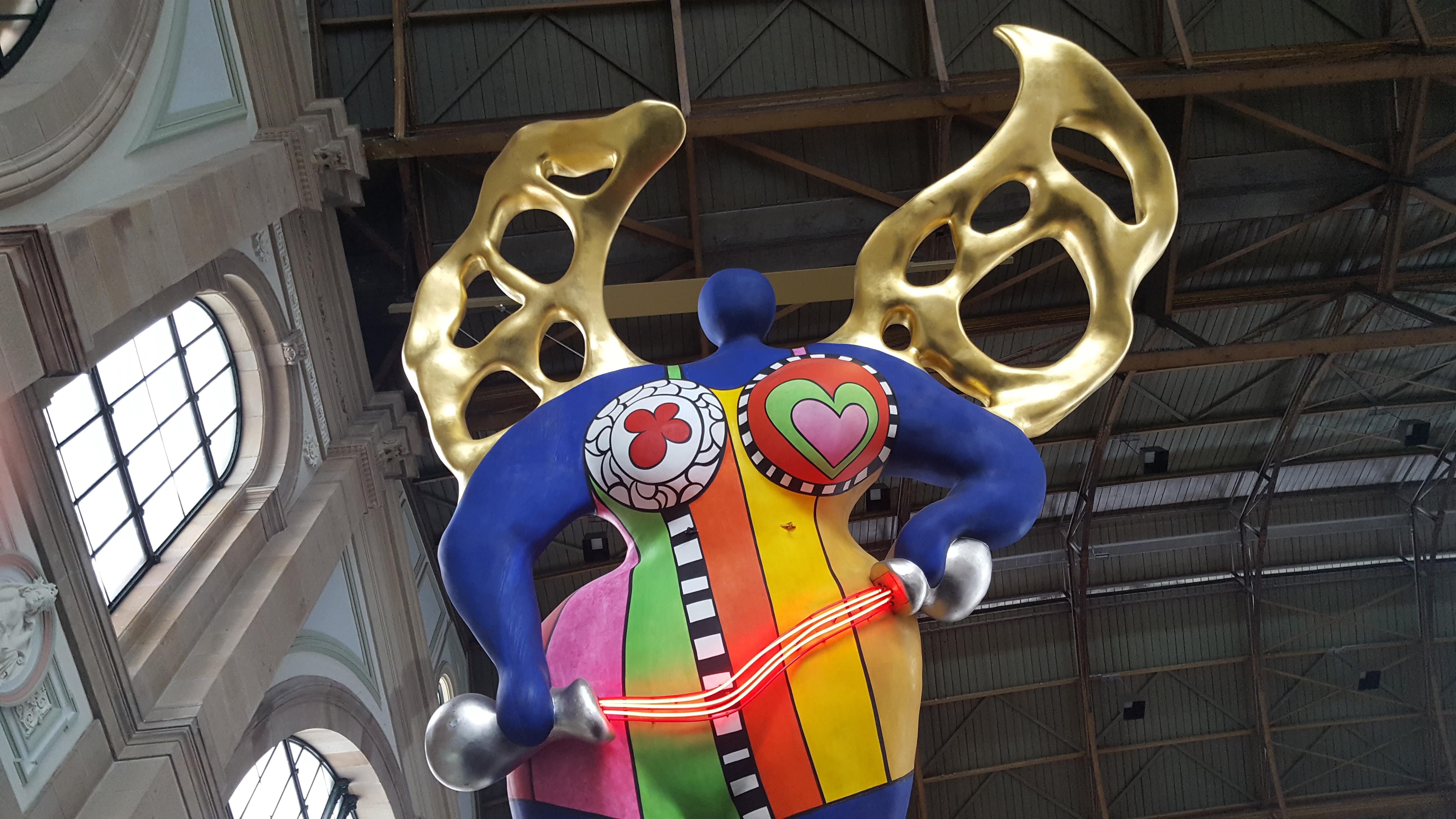 Farbiges Kunstobjekt in farbiger Engelsform unter dem Dach der Zürcher Hauptbahnhofhalle.